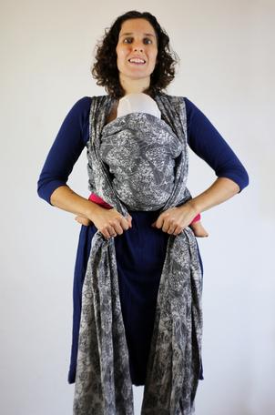 1. Zet het midden van de draagdoek onder je borstkast. Haal de banden van de draagdoek naar achteren en houd ze met één hand vast.      2. Kruis de banden van de draagdoek op je rug, zet ze op je schouders en laat ze naar voren en naar beneden lopen.      3. Spreid de banden van de draagdoek goed uit, zorg dat de bovenste zoom van de draagdoek niet gedraaid is.
